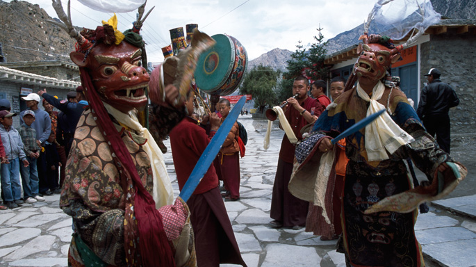 masked dancers and buddhist people dancing